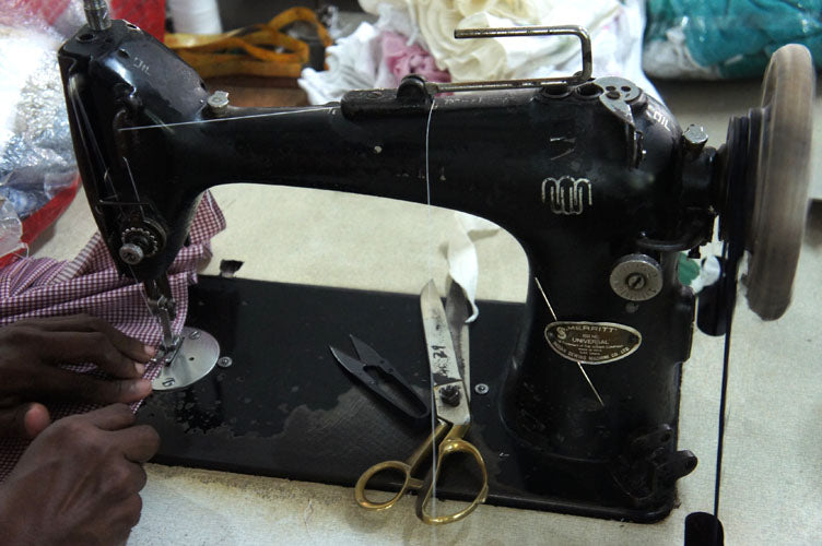 Tailor's machine with scissors and a pair of hands working