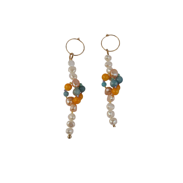 Beautiful pearl and gemstone earrings on the beach australia summer