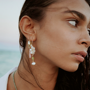 Beautiful model wearing long statement earrings on the beach at sunset