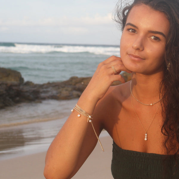 girl wearing gold and pearl jewelry on the beach