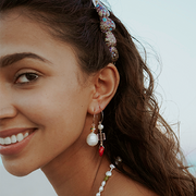 beautiful pink and red and pearl earring worn by model outside