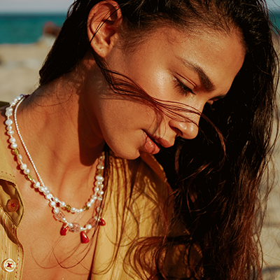 beautiful girl wearing pearl necklaces on the beach summer jewelry