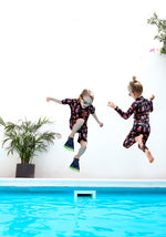 children jumping into pool wearing rash guards