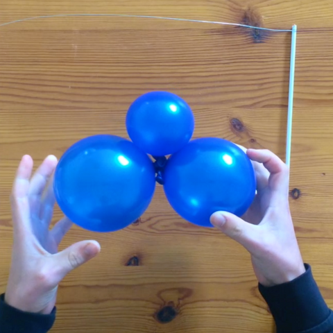 Tying sets of blue balloons for cake topper cute DIY kit
