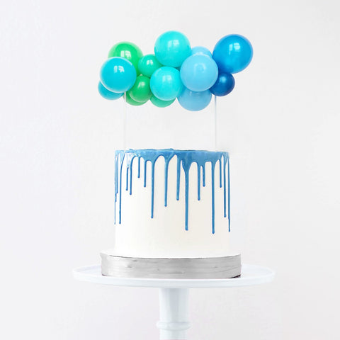 Custom blue cute balloon garland cake topper on top of blue lagoon birthday cake