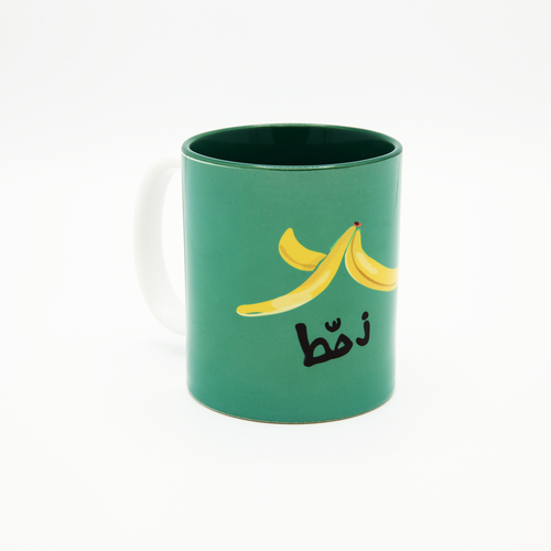 Buy online in Lebanon this coffee mug in green color with a yellow banana peal with the word Zahhet on it, meaning