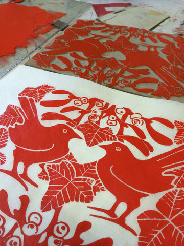 Red mistletoe lino print in progress