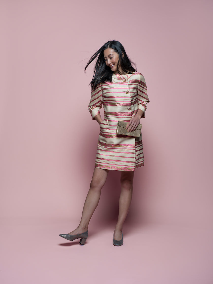 A woman wearing a pink and cream skirt suit and Julieta block heels.