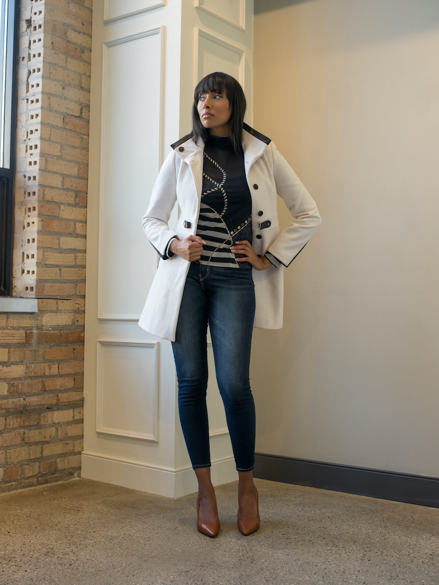 A woman wearing a white trench coat, skinny jeans and brown Julieta heels.