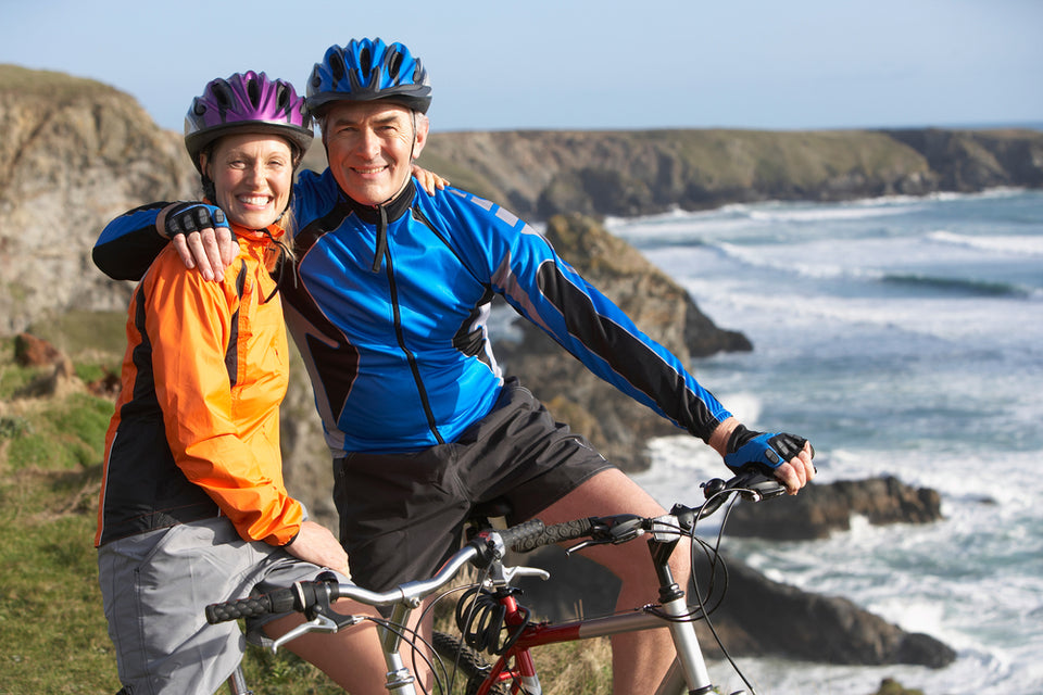 An older couple is standing above their bikes in helmets on top of a mountainous road near an ocean while smiling at the camera
