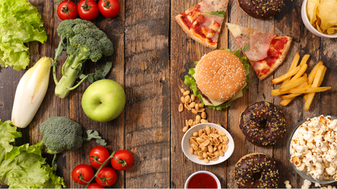 An overhead picture of healthy food such as apples, broccoli, and celery next to unhealthy fast food like burgers, fries, and pizza on a wooden table.