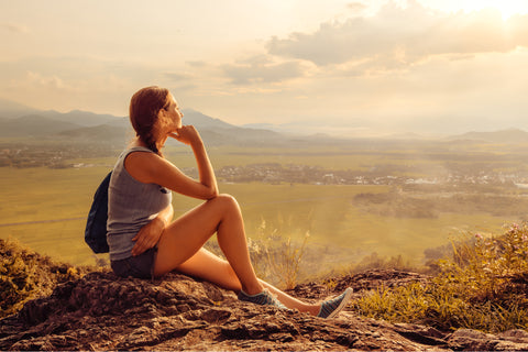 A young woman is sitting on a small plateau in shorts enjoying a sunset.