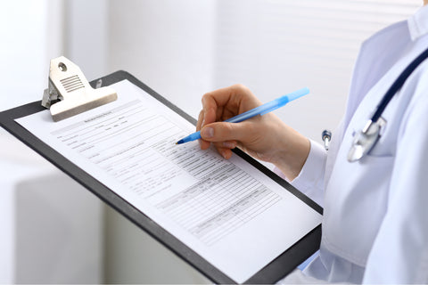 A picture was taken from the side of a physician in a white lab coat and stethoscope visible standing with a clipboard and pen in the ready–with no head showing.