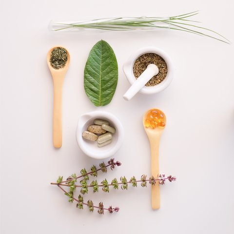 A clean, simple overhead image of herbal powders in wooden spoons next to natural compounding tools with a single green leaf and valerian flower.