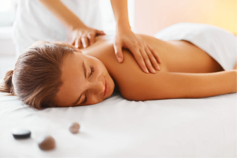 A young woman laying on a toweled table on her stomach is smiling as she's getting a massage from a masseuse whose hands are just visible in the shot.