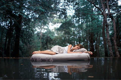 This image is a woman sleeping on a queen-size bed floating on water in the middle of a forest.