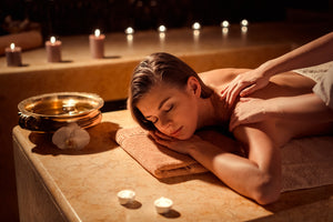 A young woman is laying down, surrounded by candles and heated rocks with her eyes closed in a soothing spa getting a massage.