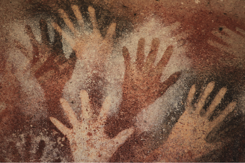 A primitive ancient cave wall with several handprints drawn on red stone to indicate prehistoric times.