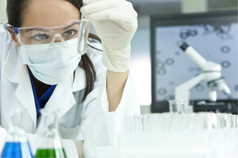 A woman in a laboratory with microscopes in the background is wearing a protective mask and safety goggles while inspecting a vial.