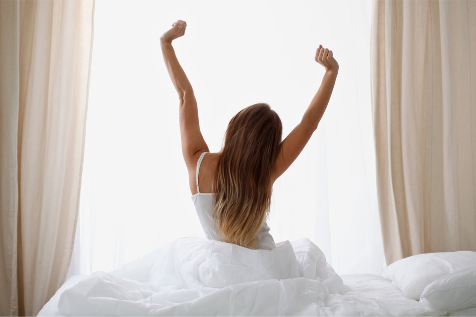 A woman is sitting on the edge of the bed facing her window while stretching to indicate she just woke up from a deep, restful sleep.