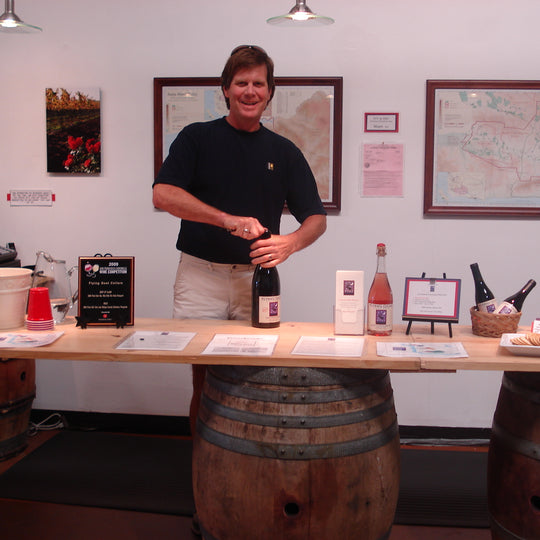 Norm Yost in the tasting room. Old table with barrels being used