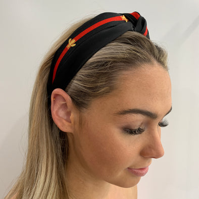 Stunning top knot black headband with red/black ribbon stripe and gold print decor.   Compliments any outfit.   One size only - imported.
