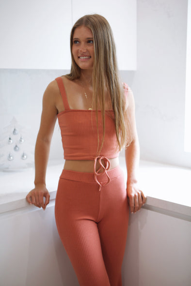 Beautiful burnt orange crop tank and pants set!   Matching quality ribbed material (95% Polyester, 5% Spandex)  Tank  Straight neckline  Non-adjustable, thick straps  Adjustable drawstring waistline  Unlined  Pants  High waisted  Fitted, elastic waistband  Model Measurements  Sophie (blonde) - typically an AUS size 6 (171cm), wears size S in this style.  Lara (brunette) - typically an AUS size 8 (169cm), wears size S in this style.