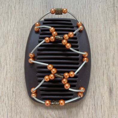 Medium brown hair clip with metallic and orange pearl coloured outer beading and copper/gold coloured centre piece.