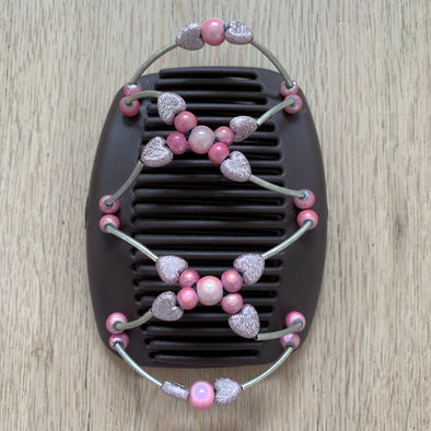 Medium brown hair clips with metallic and pink beading, with sparkly pink hearts.