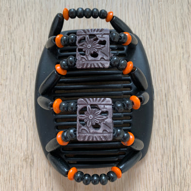 Medium black hair clip with black and orange beading, and decorative centre.