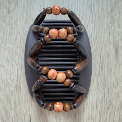 Medium brown hair clip with dark wooden beads and orange patterned centre beads.