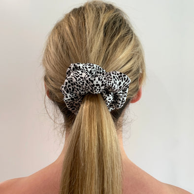 Scrunchies are back and they're here to stay! These stunning scrunchies look great in your hair and also work as gorgeous accessories.  Colour/Pattern: White with black leopard print  Material: Polyester  Washing instructions: Cold hand wash  Dimensions: Material width approximately 4 cm  Made by us in Bondi Beach  With love from Larzy xx