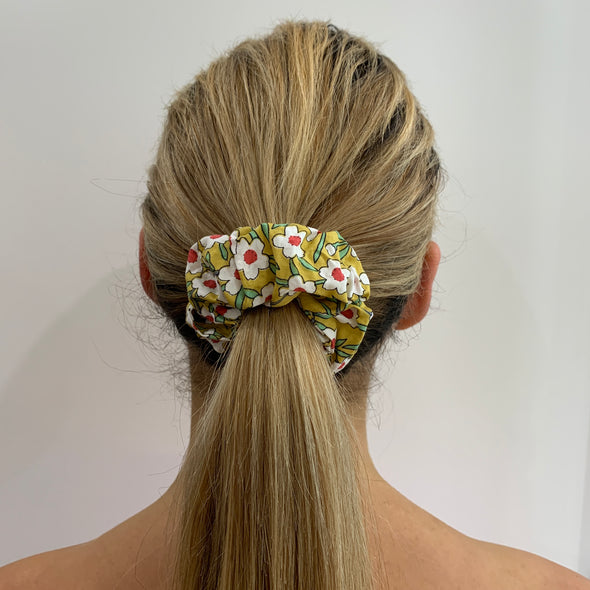 Scrunchies are back and they're here to stay! These stunning scrunchies look great in your hair and also work as gorgeous accessories.  Colour/Pattern: Mustard yellow with white flowers Material: Cotton  Washing instructions: Cold hand wash  Dimensions: Material width approximately 4 cm  Made by us in Bondi Beach  With love from Larzy xx