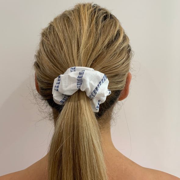 Scrunchies are back and they're here to stay! These stunning scrunchies look great in your hair and also work as gorgeous accessories.  Colour/Pattern: White with blue broken striped lines  Material: Cotton  Washing instructions: Cold hand wash  Dimensions: Material width approximately 4 cm  Made by us in Bondi Beach  With love from Larzy xx