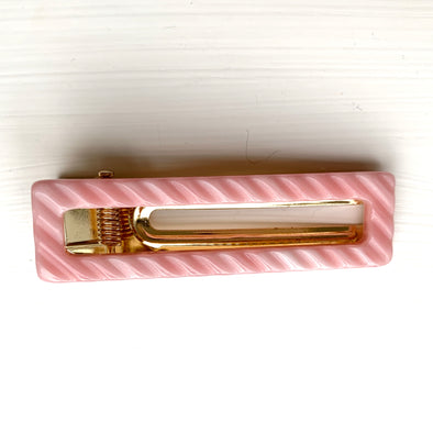 Pink ribbed hair clamp set on a gold base.