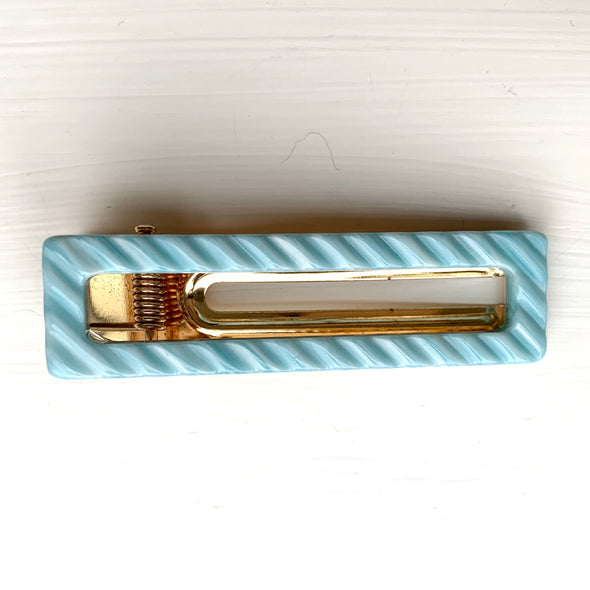Blue ribbed hair clamp set on a gold base.