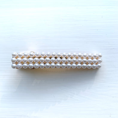 3 rows of pearls set on a gold base clamp.