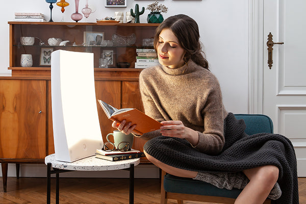 Woman reading a book using a light therapy lamp