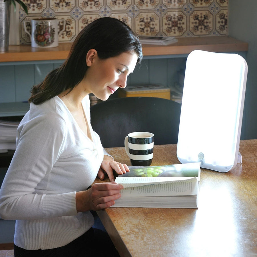 Woman using Lumie Arabica SAD lamp while reading