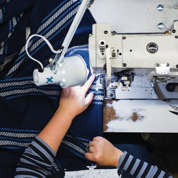Hemmer Jennifer Splude sews a double-needle hem around a swath of fabric. / Photo by Jesika Theos, Boston Magazine