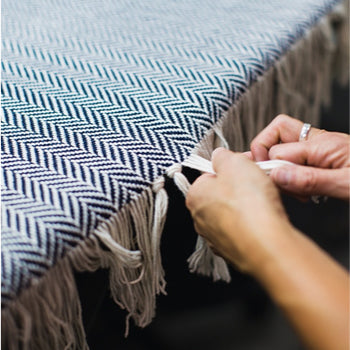 Staffer tying knots on blanket fringe / Photo by Jesika Theos, Boston Magazine