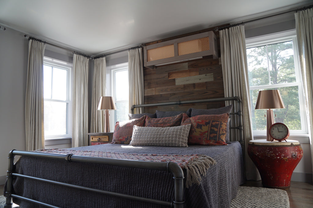 A custom DIY reclaimed headboard that reaches from floor to ceiling is attached to the wall behind the bed.
