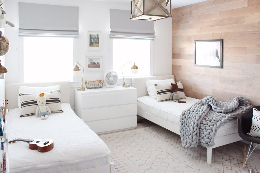 Neutral boy bedroom design with two twin size beds and rustic wood wall.