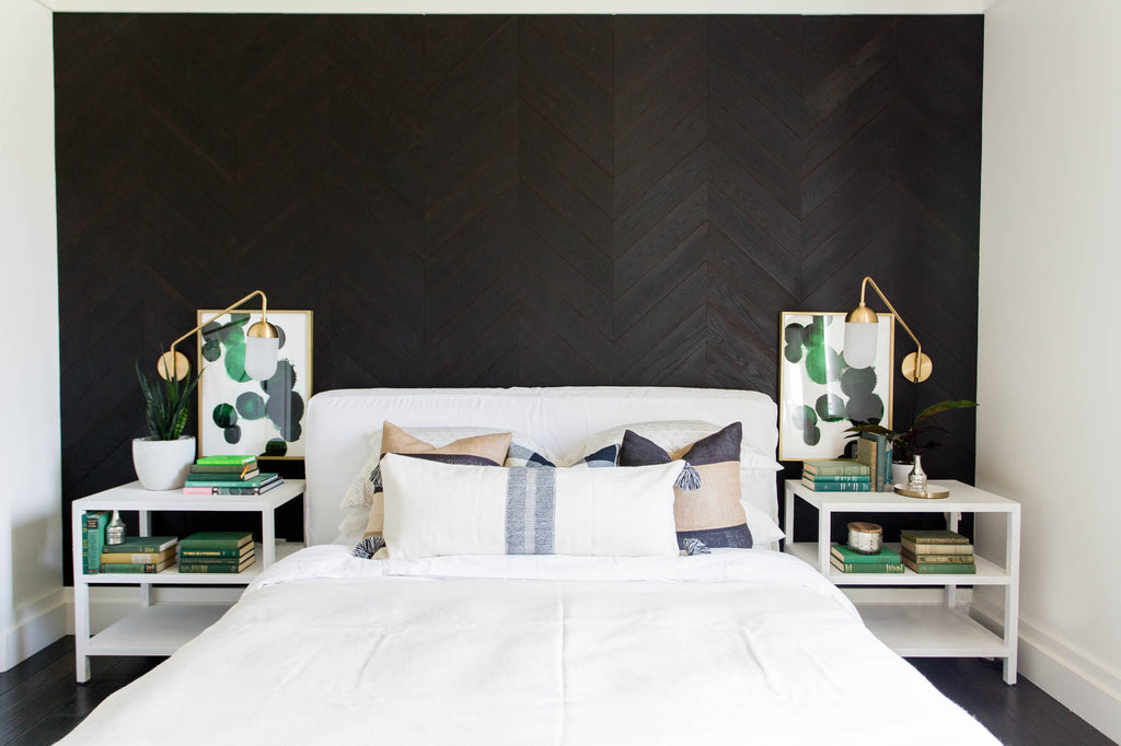Charcoal wood interior wall paneling done in a beautiful chevron design creates wow factor in a master bedroom.