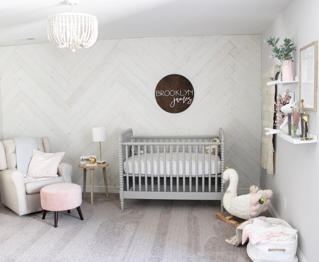 A nursery with interior wood plank walls in Hamptons done in a herringbone pattern.