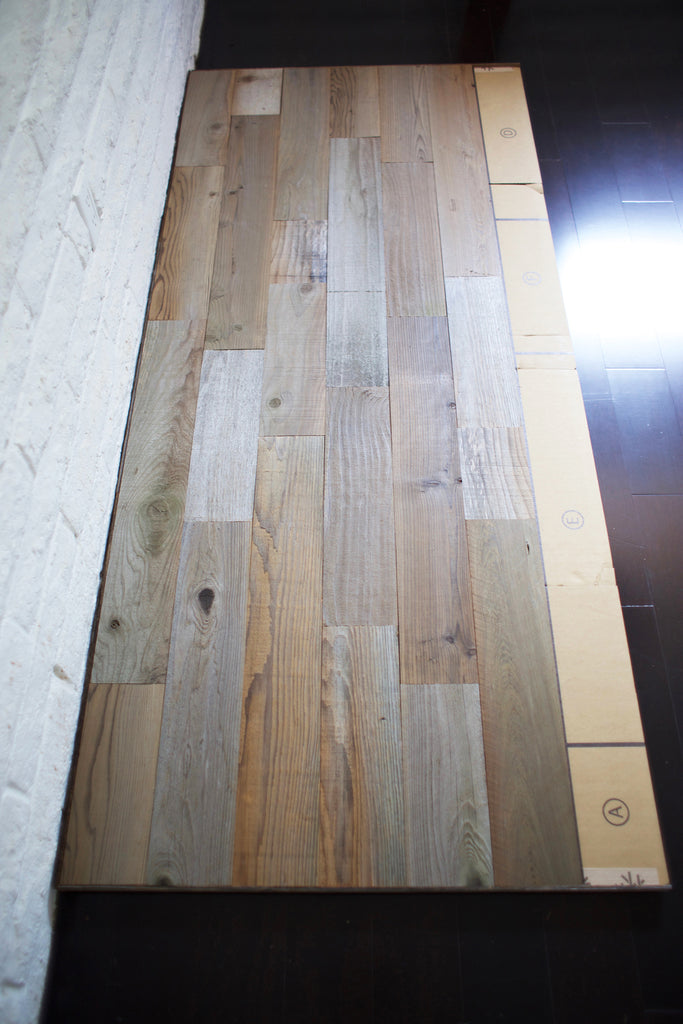 A reclaimed wood headboard diy project is laid out on the floor.