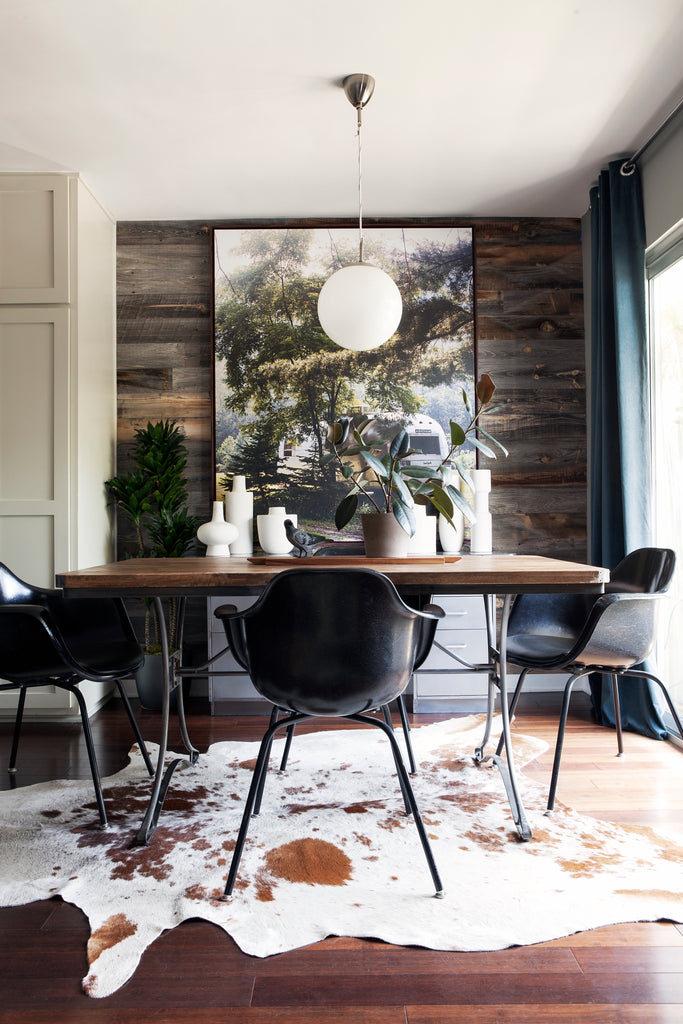 Barn wood wall paneling and a cow hide rug add rural feel to a dining room.