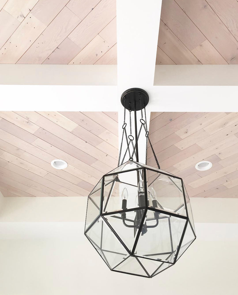 Ceiling wood planks are angled in coffered ceiling and paired with black geometric pendant light.