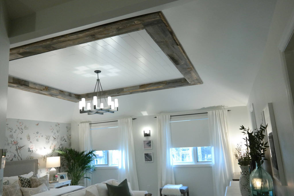 Ceiling wood planks bring eye to chandelier when they cover beams in a neutral bedroom.
