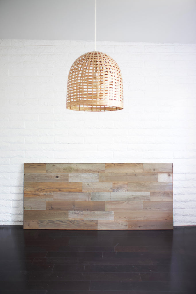 A finished reclaimed wood headboard diy project is leaning against a white brick wall.